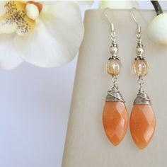 Sayomi Earrings is made of hand wire wrapped faceted apricot jade marquise cut gemstones, pale peach melon cut glass, and genuine Swarovski pearls. The French earhook is made out of silver.