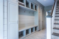 Grey mud room features wide plank gray shiplap paneled walls framing closed mud room lockers either side of a built-in cubby bench below coat hooks and overhead storage.