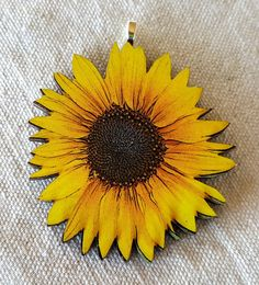 Laser cut and laser printed wood pendant. Large sunflower measures approx 2 inches by 1 3/4 inches. Made of lightweight wood with matte glaze. If