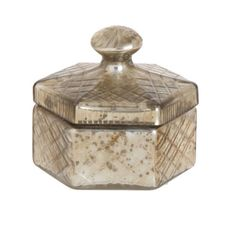 "Antiqued Glass Hexagon Box $23.95 Item #   RZ564  This beautiful and chic box is made of antiqued glass in the shape of a hexagon. It includes a lid with knob and it works nicely for keeping all sorts of things inside. Just don't use it with any food items and it should be used with dry items so the metallic finish doesn't come off. You could use it to hold some cotton swabs or other essential toiletries on the counter top. Made by Raz Imports, this box measures about 5"" wide by 5"" tall."