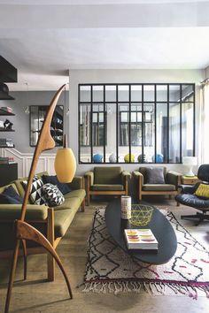 Un salon design et authentique avec des fauteuils scandinaves, un tapis berbère et des coussins à motifs géométriques