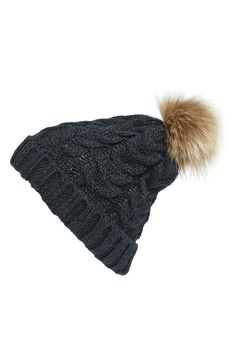 This chunky cable knit beanie topped with a plush faux-fur pompom is a surefire way to add on-trend style to any cold-weather look.
