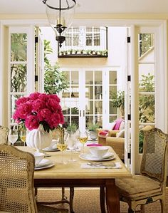 Be still my heart! French Country dining space opening onto open courtyard. Love the glass pendant light and fushia flowers!