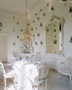 white dining with blue porcelain on brackets ~ Axel Vervoordt design (Love it but someone has to get up on a ladder and dust all those little brackets & vases…)