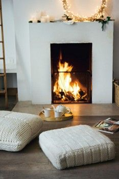 cozy white fireplace with knit floor cushions  LOVE