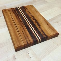 This handmade cutting board is made with Goncalo Alves, Hickory, Walnut and Purple Heart woods. Cutting board measures 9 1/4 x 6 3/4 x 7/8 thick. Board is finished with food grade beeswax and mineral oils.  Board ships wrapped with twine with a handmade cork tag.