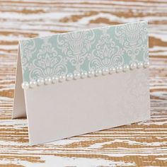 Make your own table stationery with supplies from Imagine DIY. Pretty wedding place card in aquamarine and white with pearl details