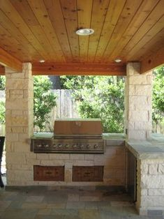 Limestone columns and outdoor kitchen in Houston, Texas with tongue and groove ceiling and slate patio.