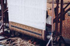 Un hombre trabajando en una prenda usando una máquina textil tradicional.