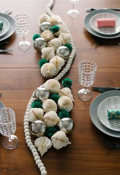 Blogger Melanie Blodgett traded place settings for DIY party poppers and substitutes a traditional table runner for tissue balls, ornaments, and felt garland.  See more at You Are My Fave.   - CountryLiving.com