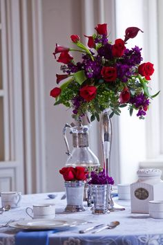 Red roses, red mini callas, red tulips, purple stock, and seeded eucalyptus. This would also look nice using an eiffel tower vase.