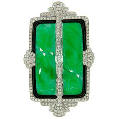 Beautiful Art Deco revival brooch / pendant. Strong geometrical pattern. Classy combination of white diamonds, green jade and black enamel.        The piece features a floral motif carved jade set in a black enamel frame and studded all over with round diamonds. The brooch is accentuated with a marquise cut diamond in the center. 21st century
