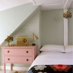 Bedroom: Modern Retro: Pastel modern retro bedroom in attic alcove sloping ceiling