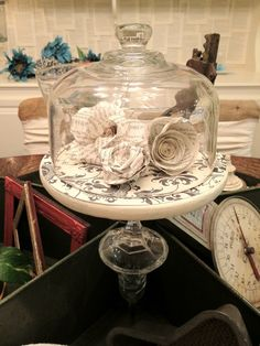 Paper flowers made from the pages of old books. I used this to fill an old cheese plate/cloche I purchased at a yard sale.
