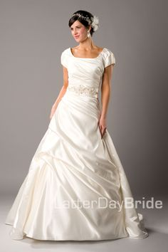 This silky satin A-line gown has a ruched bodice with embellishment placed on the natural waistline. It has a slightly rounded square neckli...