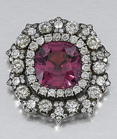 1880s brooch centering on a cushion-shaped spinel within a surround of circular-cut diamonds,