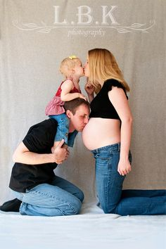 Adorable maternity shot!  Big sister on daddy's shoulders, daddy kissing momma's belly and big sister kissing momma. :)