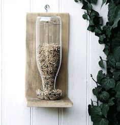 Just in case you needed another re-use for your old glass bottles, this simple DIY bird feeder is made using scrap wood, wire, a hook, the by tanisha
