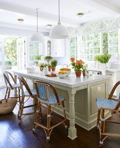 Our expert says your garden can be your best source of design inspiration, and interiors that are just extensions of your exteriors will shine. Here, he complements the blue-and-white French bistro stools and sky-blue walls (painted in Borrowed Light by Farrow & Ball) with a mossy green island. Click through for more blue and white home design ideas.