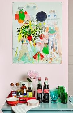 Pastel pink walls with colorful artwork, blue coffee table, blue and green glass cups, assortment of beverages and vitamins,  red tray, patterned bowl, and a pink flower in a white vase // Lena Duhma's New York dressing room