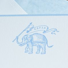 Children's Stationery   Bone white Corinne card, hand bordered in powder blue, letterpress imprinted with elephant motif and name in banner in powder blue, envelopes hand lined with light blue tissue