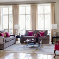 Classic sofas and a restrained colour scheme of pale neutrals create a sense of calm in this stylish living room. A large rug adds warmth to the blond wood flooring and matches the curtains. Matching side table lamps add a touch of formal symmetry, while pink accents give the scheme a lift.
