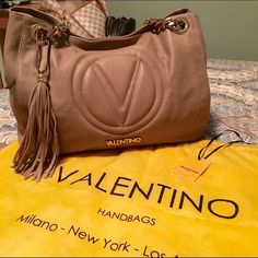 """Valentino by Mario Valentino Vera Bag Vera leather shoulder bag by Valentino in Like New condition!   Only worn once as I think it may be a little too large for my frame(5""""4""""/117lbs for reference).   Love this bag and may just keep it if it doesn't sell for a fair price on Posh.  Color is like a taupe/tan and goes w everything!  Only imperfection is a set of marked numbers inside the zipped smaller pocket(see pic).  11""""H/15""""W/13""""Strap Drop/7.5""""D Valentino Bags Shoulder Bags"""