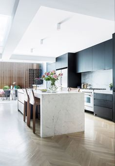 Black poly kitchen cabinets, white marble island benchtop with waterfall edge, pale timber herringbone floor, marble splashback