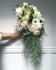 Cascading wedding bridal bouquet made with light pink garden roses and white ranunculus