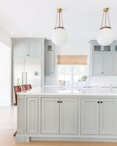 Kitchen design by Amber Interiors, photo by Tessa Neustadt Rejuvenation Hood Classic Globe pendant via Architectural Digest