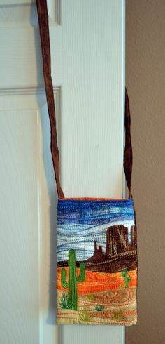 This fully lined bag may be worn cross body to carry cell phone, keys and other small items. Strap is thin enough to be gently tied in a knot to shorten it. It was made with high quality fabrics and embroidery threads. The sky is embellished with metallic thread. This wonderful bag measures 5-1/2w x 8h.