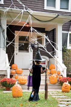 Two rows of jovial jack-o-lanterns guide cautious guests toward the door. Soccer goal netting is draped halfway over the roof, offering a clever method to attach webs and giving one spider a fun way to greet newcomers.