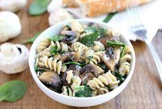Pasta met spinazie, geitenkaas & paddestoelen  90 gr pasta 200 gr champignons, in tweeën gesneden 300 gr spinazie, grof gehakt75 gr geitenkaas, verkruimeld 1 teentje knoflook, gehakt 1 el olijfolie 0,5 el balsamico azijn 2 el vers gehakte basilicum zout en zwarte peper, naar smaak