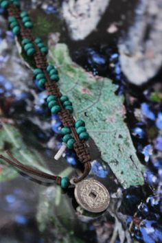 Bracciale K'un ☷ Materiale: Cotone cerato marrone e perline in legno verde, monetina I Ching portafortuna  Lavorazione: Macramè  Significato: K'un ☷ è uno degli 8 trigrammi del Libro dei Mutamenti cinese. E' il trigramma della Terra ed è composto di sole linee Yin rappresenta in ogni suo aspetto la capacità di ricevere, di accogliere, di sostenere, di far crescere e di portare a compimento.