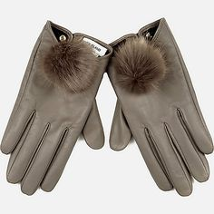 Give your outfits a seriously sophisticated finish with these premium grey leather gloves. Sleek and so chic, they're finished with a plush pom pom.