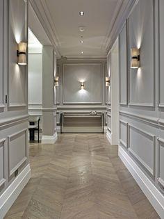 boiserie murale décorative en gris clair et parquet à chevrons pour anoblir le couloir