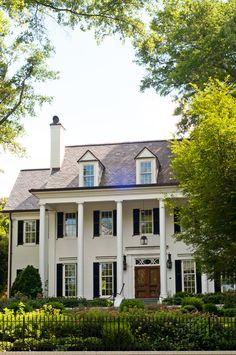 White painted brick, black shutters, dormers, lantern, natural wood door