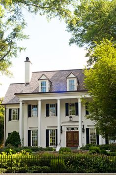 White painted brick, black shutters, dormers, lantern, natural wood door