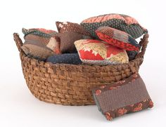 Pennsylvania rye straw basket, 19th c. and old quilt pincushions