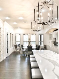 The marble countertops set off this black and white kitchen and dining space.