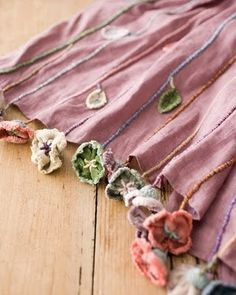 I love this... I think it's a scarf (although it could be the hem of a skirt?), and the couched 'stems' end in dangly fabric flowers... very very pretty indeed.