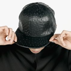 Textured leather snapback cap. With a texture similar to ostrich leather, this street style staple gains a luxurious feel. With its adjustable snapback closure, firm brim, and rounded crown, this cap will best accessorize street wear or a casual look.