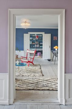 COLOR: At Copenhagen's The Apartment, a cherry-colored Hans Wegner PP129 armchair takes center stage. A blue McCollin Bryan Tinted Lens table rests nearby.