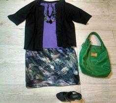 Saia estampada em lilas, blusa lilas, casaco preto, sapato preto, bolsa verde, colares preto e verde.