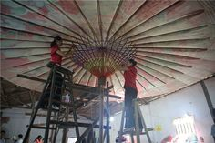 Two women work on a giant oil paper umbrella in Fenshui town, Sichuan Province, Southwest of China......Wow it looks amazing & Beautiful