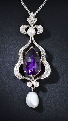 An elegant Edwardian Amethyst, Diamond, and Freshwater Pearl Pendant features a rich, vivid Amethyst surrounded by ribbons of Diamonds. The pendant is topped by freshwater Pearl and Diamond Fleur-de-Lis and finished with a glowing freshwater Pearl drop. This beauty is set in Platinum over 18 karat yellow Gold and suspended from an 18 inch Platinum chain.|| Lang Antiques.