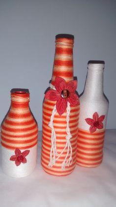 Garrafas decoradas com barbante mesclado laranja e branco, detalhes na frente e feltro abaixo da peça.