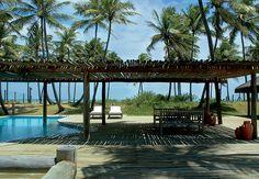 A vegetação de restinga, preservada e recuperada pelas paisagistas Arilda e Dange Cardoso, envolve o deque, que tem pérgola feita com caibros de eucalipto. A área mais rasa da piscina esconde um banco de alvenaria. A casa fica na praia de Busca Vida, em Salvador