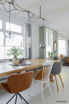There is a scandi hygge feel to this dining room and I like the use of different chairs and pendants to add interest to the interiors next to the light, calming colours.