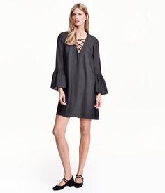 Kort kjole med let vidde i strukturvævet kvalitet. Den har V-udskæring med krydsede bånd i udskæringen. Lange ærmer med flæse ved håndleddet.
